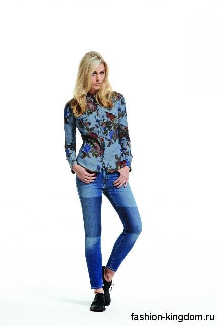 Синие джинсы фасона скинни с асимметричным окрасом из коллекции Jacob Cohen сочетаются с джинсовой рубашкой синего тона с цветочным принтом и черными туфлями на низком ходу.