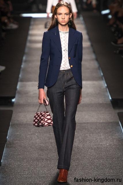 Джинсы с высокой талией темно-серого цвета сочетаются с белой ажурной блузкой, пиджаком королевского синего тона, маленькой сумочкой и коричневыми ботильонами от Louis Vuitton.