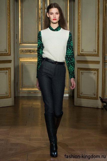 Узкие черные джинсы с высокой талией в тандеме с белой безрукавкой, блузкой черно-зеленой расцветки и высокими черными сапогами на каблуке от Vanessa Seward.