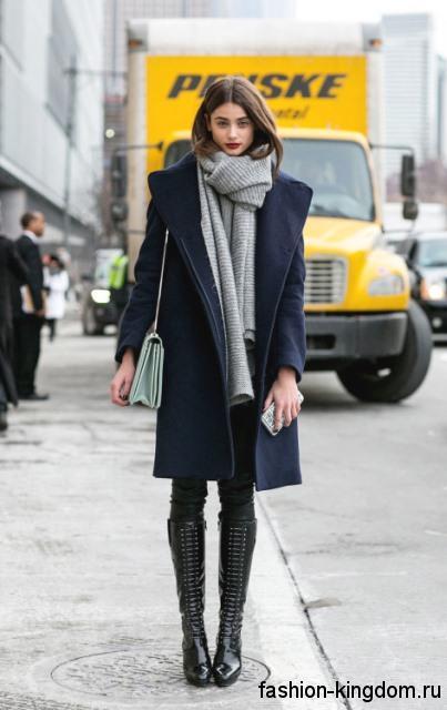 Зимний широкий шарф светло-серого оттенка в сочетании с пальто полуночно-синего тона, черными брюками и высокими сапогами черного цвета на каблуке.