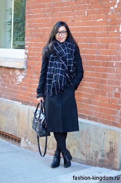 Пальто черного цвета длиной ниже колен сочетается с широким шарфом бело-синего тона в клетку, черной сумкой и ботильонами на широком каблуке.