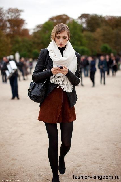 Короткая черная куртка сочетается с объемным шарфом белого цвета, небольшой сумочкой и туфлями черного тона.