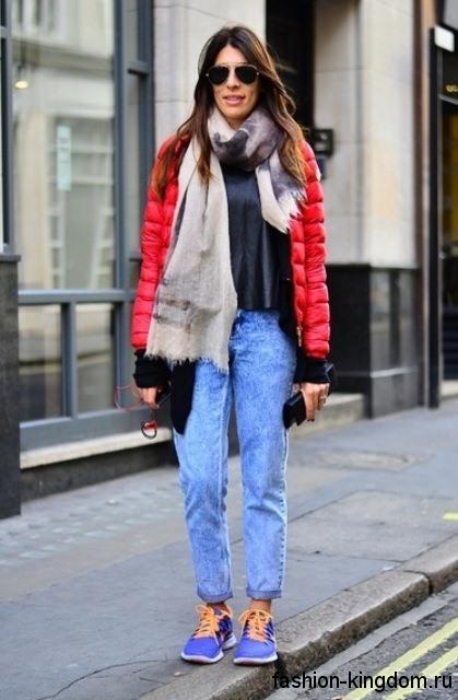 Короткий пуховик красного цвета дополняется легким шарфом серо-бежевой расцветки, синими джинсами прямого кроя и кроссовками ярко-синего оттенка.
