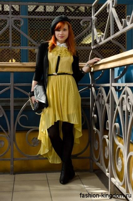 Асимметричное праздничное платье желтого цвета, свободного фасона дополняется короткой черной кофточкой, аксессуарами и ботильонами черного тона.