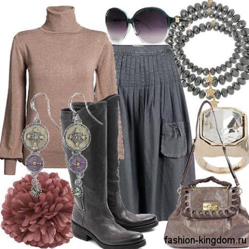 Кожаные сапоги черного цвета на низком ходу в сочетании с юбкой-миди темно-серого тона, коричневой кофточкой и аксессуарами серой гаммы.