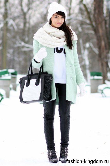 Короткое пальто светло-бирюзового оттенка гармонирует с белым шарфом и шапкой, сумочкой черно-белой расцветки и ботильонами черного тона на низком ходу.