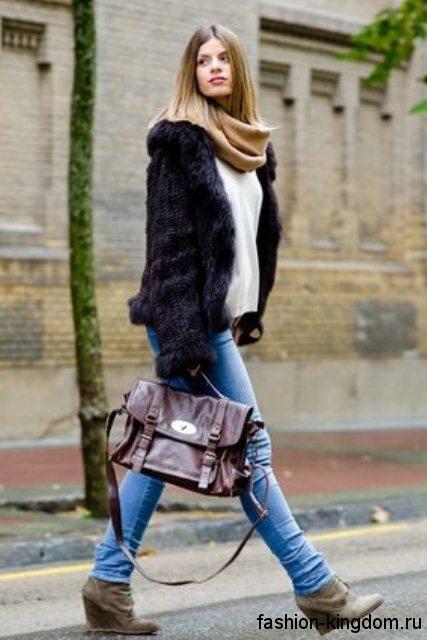 Черная шуба из искусственного меха в сочетании с шарфом коричневого тона, белым свитером, узкими голубыми джинсами и ботильонами серо-коричневого оттенка на платформе.