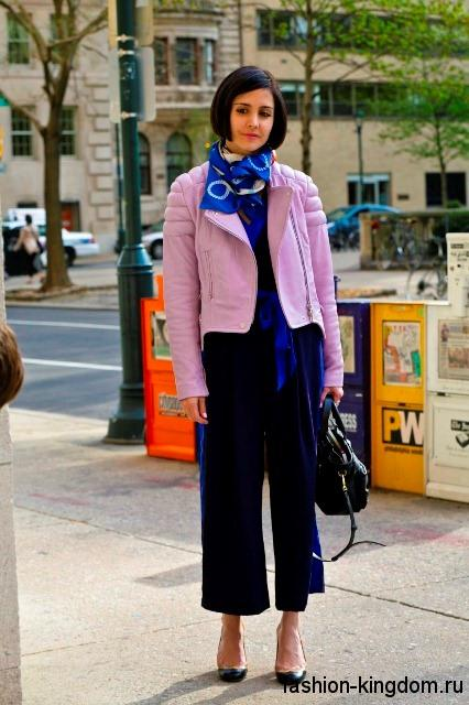 Небольшой атласный шарфик синего тона дополнит короткую куртку розового цвета, комбинезон черно-синей расцветки, сумочку и туфлями черного тона.