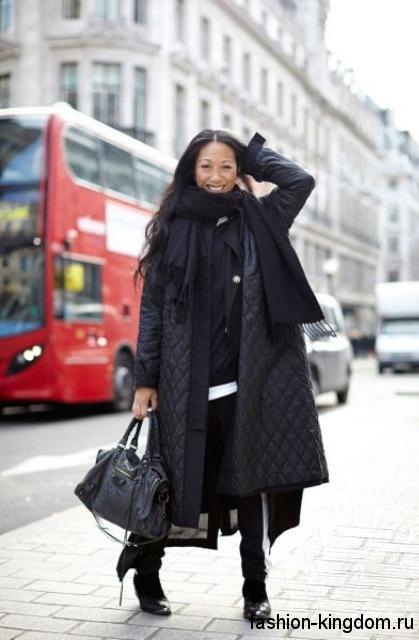 Длинная модель пуховика черного цвета сочетается с осенним шарфом черного тона, сумочкой и ботильонами черной расцветки.
