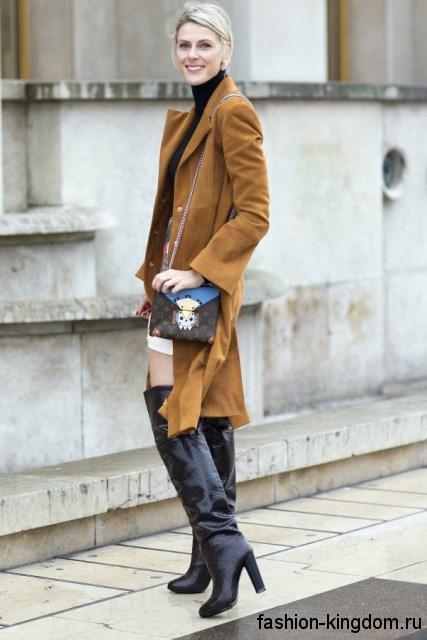 Женские сапоги выше колен черного цвета, на устойчивом каблуке дополняют весеннее пальто горчичного оттенка.