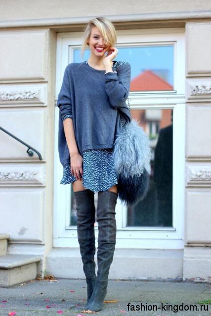 Женские сапоги-чулки темно-серого цвета на тонком каблуке в сочетании с коротким синим платьем, свитером серо-синего оттенка и меховой сумочкой синей расцветки.