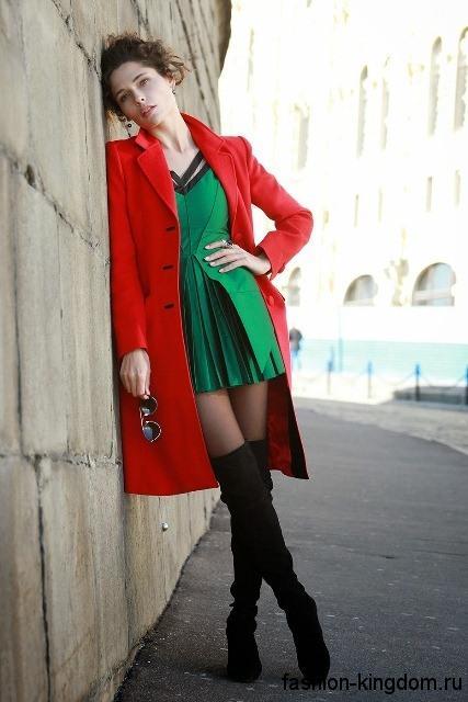 Стильное короткое платье зеленого цвета на торжество, с приталенным верхом и юбкой-плиссе в сочетании с красным пальто и высокими замшевыми сапогами черного тона.