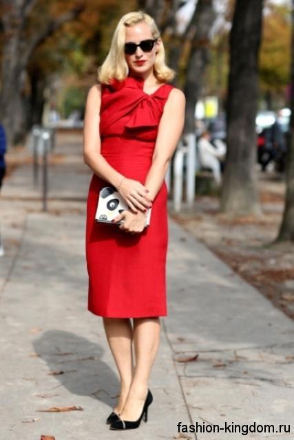 Праздничное платье красного цвета длиной чуть ниже колен, без рукавов, с акцентом на талии гармонирует с классическими черными туфлями на каблуке.
