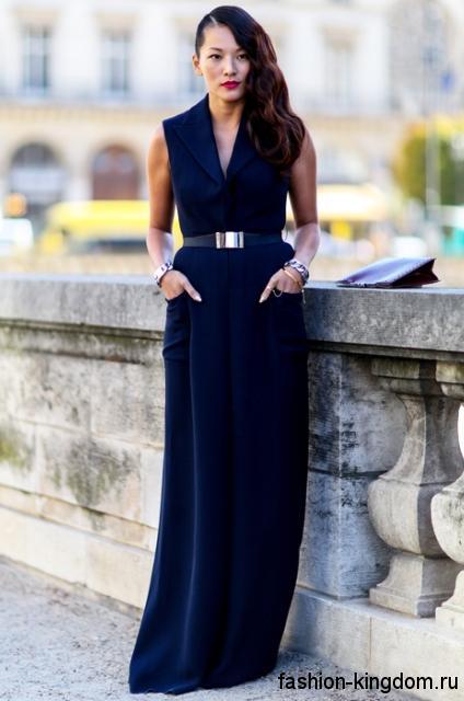 Длинное новогоднее платье королевского синего цвета, прямого кроя, без рукавов, с V-образным вырезом и тонким поясом.