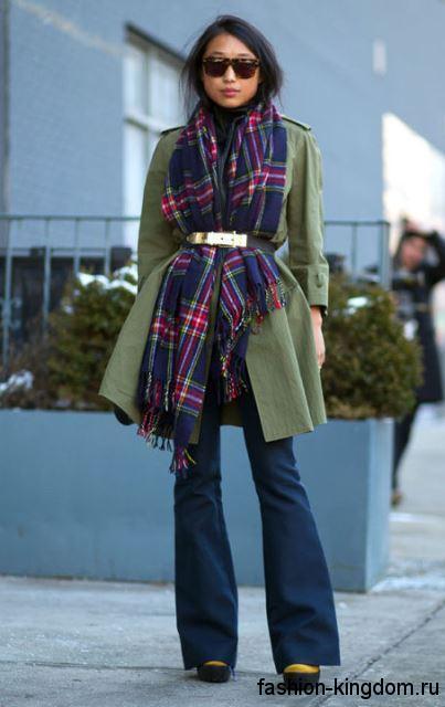 Красивый способ завязывания широкого шарфа на пальто зеленого оттенка, длиной выше колен, с широким поясом.