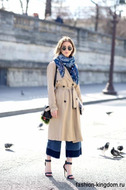 Двубортное демисезонное пальто бежевого цвета в тандеме с шарфом синего тона с белым рисунком и синими босоножками на высоком каблуке.