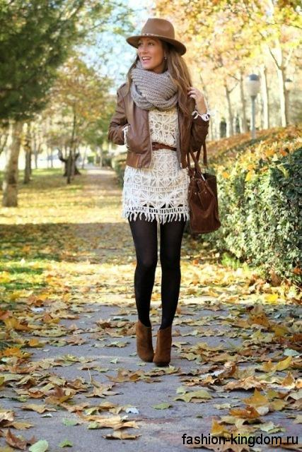Вязаный широкий шарф серого цвета гармонирует с короткой кожаной курткой коричневого тона, ажурным белым платьем, аксессуарами и обувью коричневых оттенков.