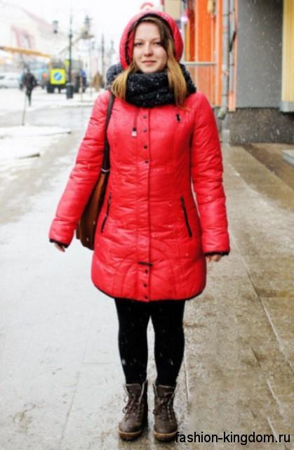 Зимний пуховик красного цвета приталенного фасона в тандеме с шарфом черного тона, объемной шапкой красной расцветки и ботинками темно-коричневого оттенка.