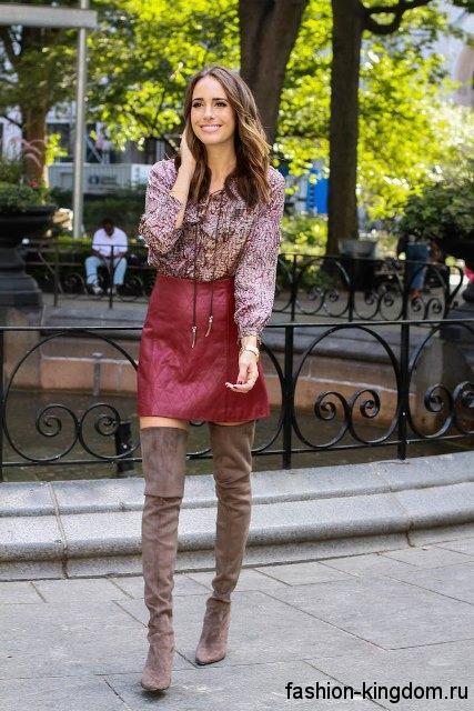 Стильные сапоги-чулки серо-коричневого оттенка на высоком каблуке сочетаются с короткой кожаной юбкой бордового цвета и блузкой серо-бордового тона.