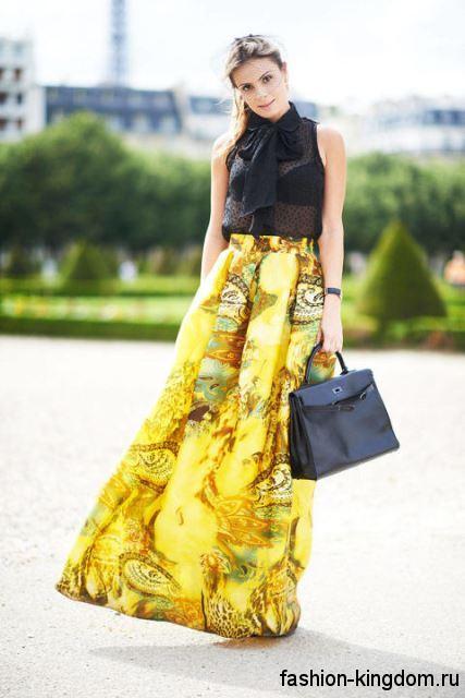 Длинная юбка желтого цвета с абстрактным рисунком, свободного кроя для вечернего стиля в тандеме с полупрозрачной черной блузкой без рукавов, декорированной жабо.