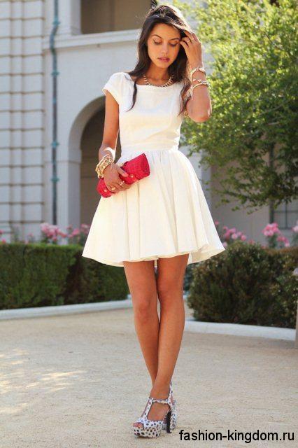 Новогоднее платье белого цвета с пышной юбкой, длиной выше колен, с короткими рукавами в тандеме с босоножками черно-белого тона на устойчивом каблуке.