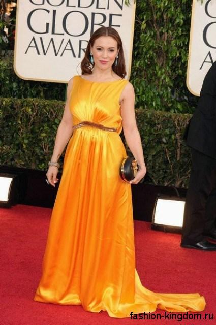 Атласное длинное платье со шлейфом желтого цвета, свободного кроя, декорированное стразами на талии, дополняется клатчем черно-золотистой расцветки.