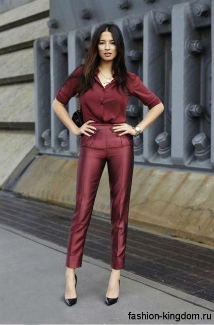 Укороченные кожаные брюки бордового цвета для вечернего стиля гармонируют с блузкой бордового тона и классическими туфлями на каблуке.