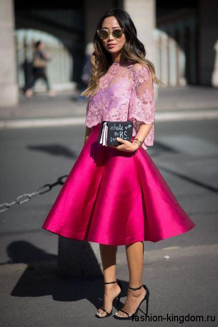 Юбка-солнце длиной миди, цвета фуксии для вечернего стиля гармонирует с кружевной блузкой бледно-сиреневого оттенка с рукавами до локтей и черными босоножками на высоком каблуке.