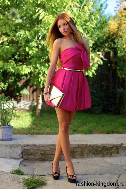 Короткое новогоднее платье розового цвета с приталенным верхом и объемной юбкой, украшенное золотистым пояском, в сочетании с черными туфлями с шипами.