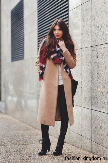 Клетчатый широкий шарф сочетается с пальто светло-коричневого оттенка и ботильонами черного тона на среднем каблуке.