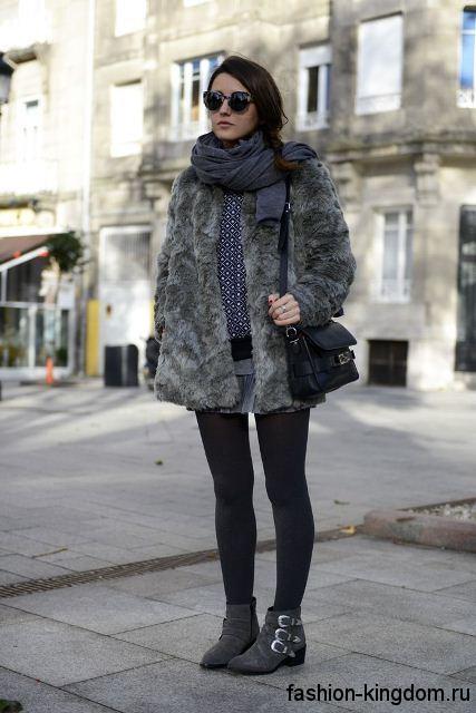 Женская шуба серого цвета сочетается с объемным шарфом темно-серого оттенка, небольшой черной сумочкой и ботильонами серого тона на низком каблуке.