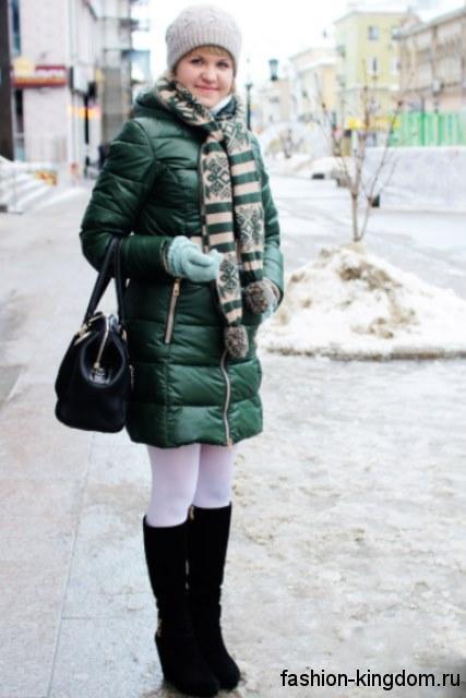 Модный пуховик темно-зеленого оттенка приталенного кроя гармонирует с шарфом бежево-зеленой расцветки с рисунком, серой шапкой, сумочкой и высокими сапогами черного тона.