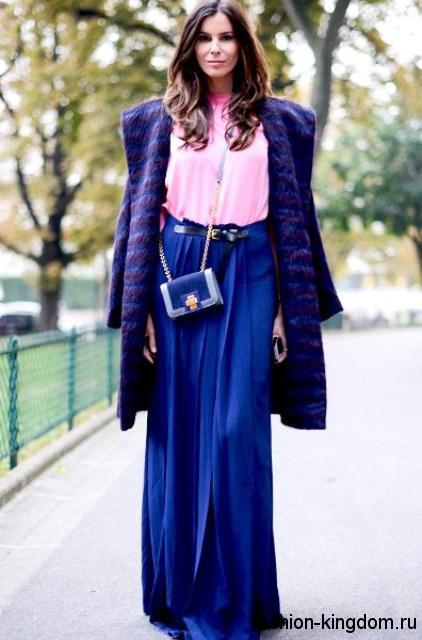 Длинная юбка синего цвета свободного кроя для вечернего стиля в сочетании со светло-розовой блузкой, пальто ярко-синего оттенка и маленькой сумочкой синего тона.