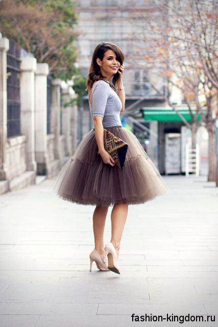 Пышная юбка серо-фиолетового оттенка, длиной до колен для вечернего стиля в сочетании с блузкой серого цвета с открытой спиной и бежевыми туфлями на тонком каблуке.