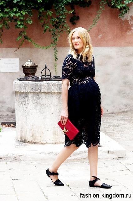 Ажурное черное платье длиной до колен, прямого силуэта, с короткими рукавами сочетается с красным клатчем и открытыми туфлями черного тона на низком ходу.