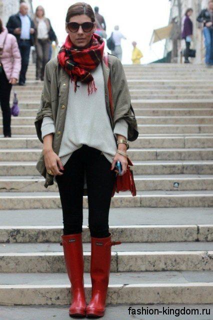 Женский шарф красно-черного цвета в клетку гармонирует с курткой-ветровкой серого тона, свитером светло-серого оттенка, черными брюками, маленькой сумочкой и высокими сапогами красной расцветки.