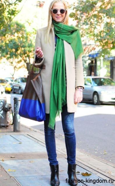 Женское весеннее пальто бежевого оттенка в сочетании с тонким зеленым шарфом, узкими синими джинсами и ботильонами черного цвета на каблуке.
