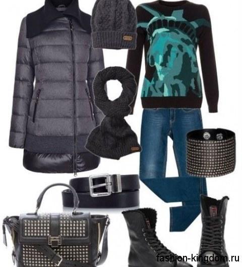 Женский пуховик темно-синего оттенка длиной выше колен в сочетании с вязаной шапкой и шарфом грифельного цвета, синими джинсами, свитером черно-бирюзовой расцветки, аксессуарами и ботинками черного тона.