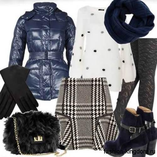 Короткий пуховик синего цвета в тандеме с вязаным шарфом полуночно-синего оттенка, белой туникой, короткой юбкой черно-белой расцветки с клетку, меховой черной сумочкой и ботильонами темно-синего тона на широком каблуке.