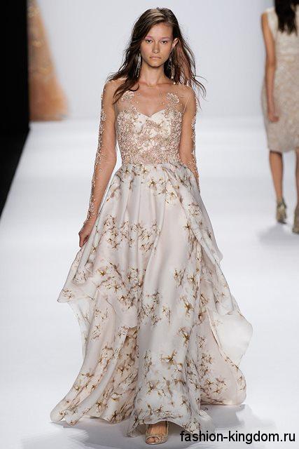 Вечернее длинное платье белого цвета с цветочным принтом, с корсетным верхом, длинными ажурными рукавами и открытыми туфлями золотистого оттенка от Badgley Mischka.