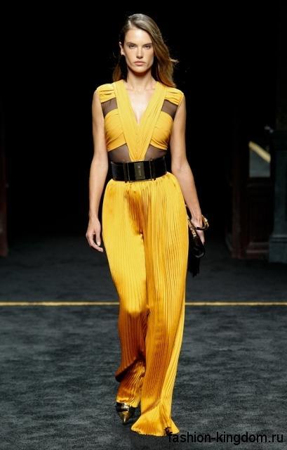 Комбинезон ярко-желтого цвета в вечернем стиле, выполненное из струящейся блестящей ткани, с V-образным вырезом и широким поясом в сочетании с лакированными туфлями от Balmain.