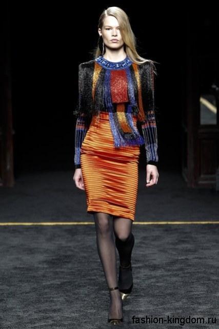 Юбка-карандаш оранжевого тона для вечернего стиля сочетается с разноцветной блузкой, декорированной бахромой, с длинными рукавами и лакированными туфлями от Balmain.