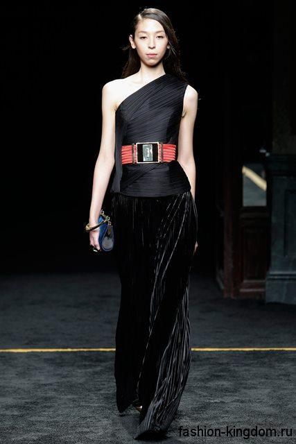 Стильное новогоднее платье черного цвета в пол, с проймой на одно плече, декорированное широким красным поясом, в сочетании с синим клатчем от Balmain.
