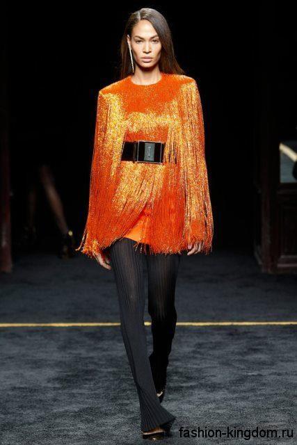 Стильная туника ярко-оранжевого цвета с черным широким поясом, выполненная из блестящей ткани, в сочетании с тонкими брюками-клеш черного тона и туфлями в тон от Balmain.
