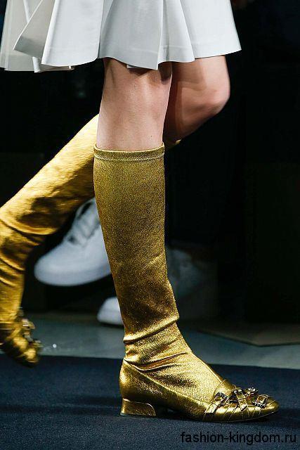 Женские сапоги золотистого цвета на низком ходу, декорированные пряжками, из коллекции Bottega Veneta.