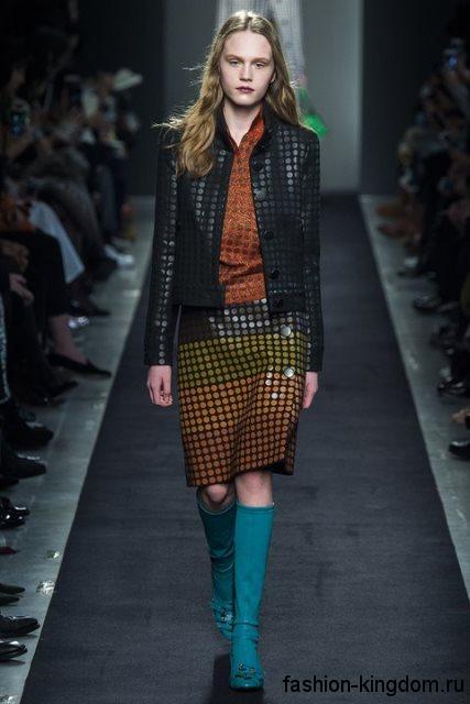Высокие сапоги бирюзового цвета без каблука, дополненные пряжками, в сочетании с короткой черной курткой от Bottega Veneta.