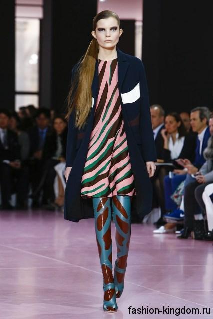 Сапоги-чулки бирюзово-коричневой расцветки, на тонком каблуке дополняют короткое платье розового цвета с абстрактным принтом и демисезонное пальто темно-синего тона от Christian Dior.