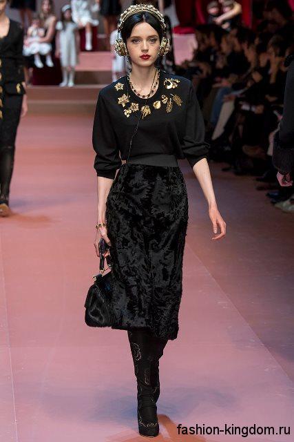 Высокие сапоги черного тона дополняют юбки-миди черного цвета и блузкой черной расцветки с золотистыми вставками модного сезона осень-зима 2015-2016 от Dolce & Gabbana.