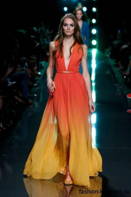 Длинное вечернее платье желто-кораллового цвета в стиле омбре, с глубоким V-образным вырезом в тандеме с открытыми туфлями в тон наряда от Elie Saab.