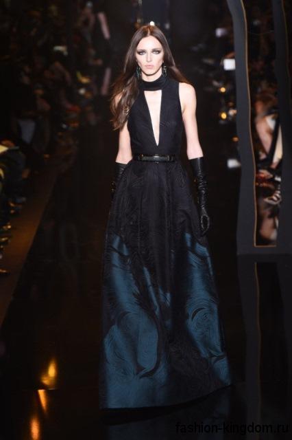 Вечерний стиль с длинным платьем полуночно-синего цвета с расширенной юбкой и глубоким V-образным вырезом в тандеме с длинными перчатками черного тона от Elie Saab.